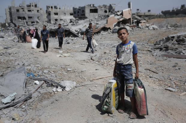 Palestinians carry their belongings after salvaging them from their destroyed house in the heavily bombed town of Beit Hanoun, in the Gaza Strip, close to the Israeli border