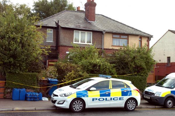 Police at the house in Wigan Road, Leigh, where the woman's body was found.