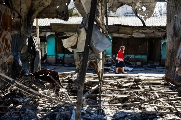 A woman passes by shops burned by shelling in Donetsk, Ukraine