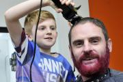 Craig Billington, from Westhoughton, has raised £600 for Cancer Research UK after a headshave and beard dye. Pictured with his son Ralph, aged eight