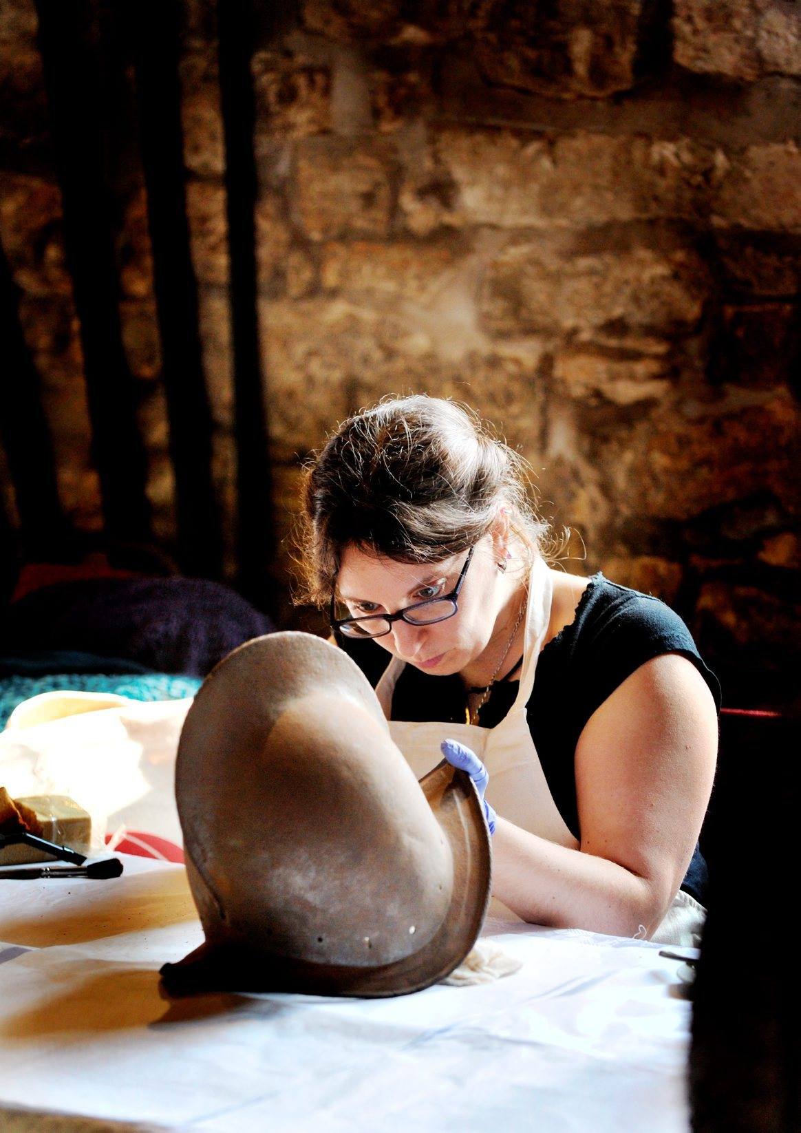 Conservator Pierrette Squires pictured cleaning armour, a pikeman's corselet and helmet from around 1620 at Smithills Hall