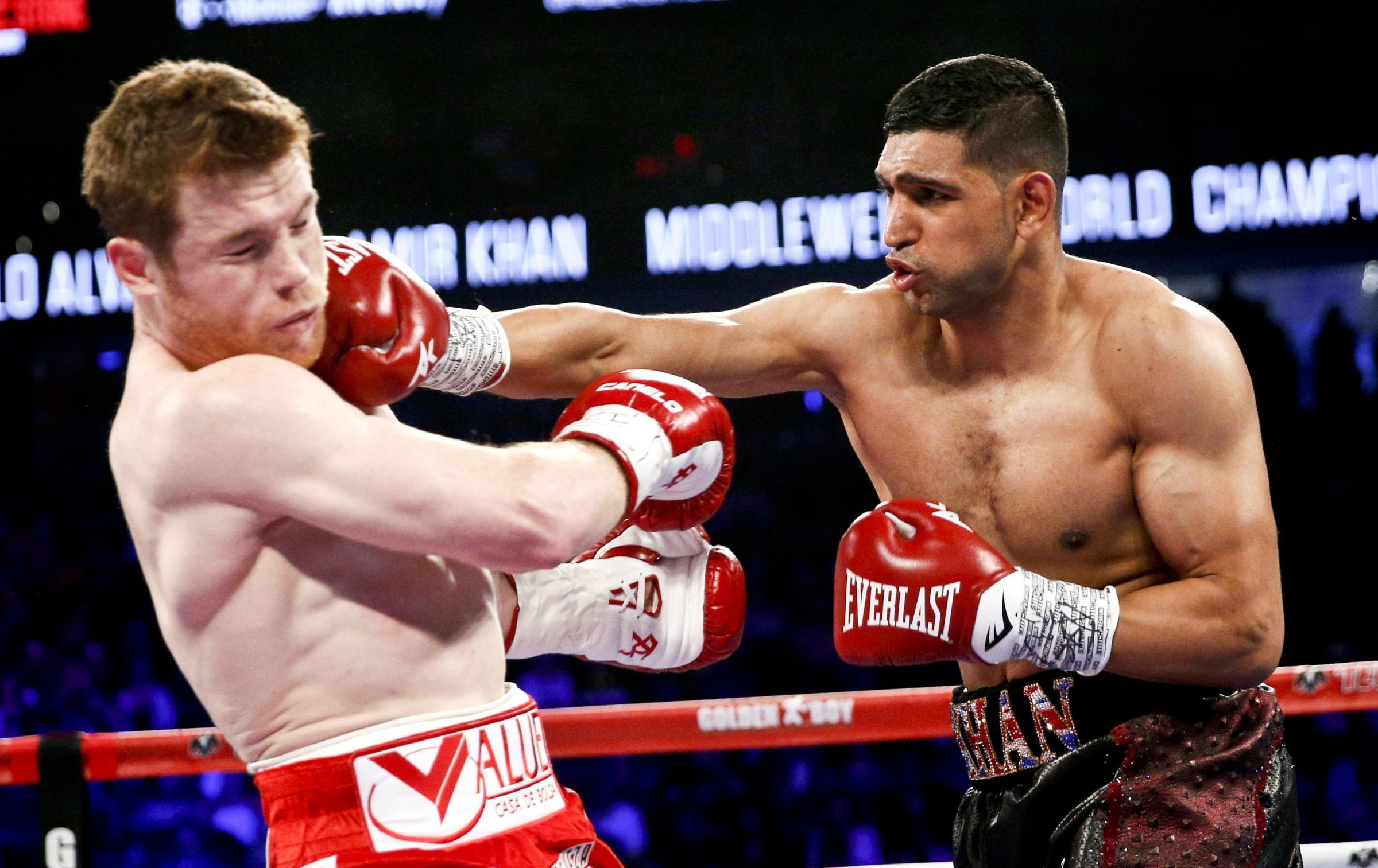 "Amir Khan, right, connects with a punch in his last fight against Saul ""Canelo"" Alvarez"