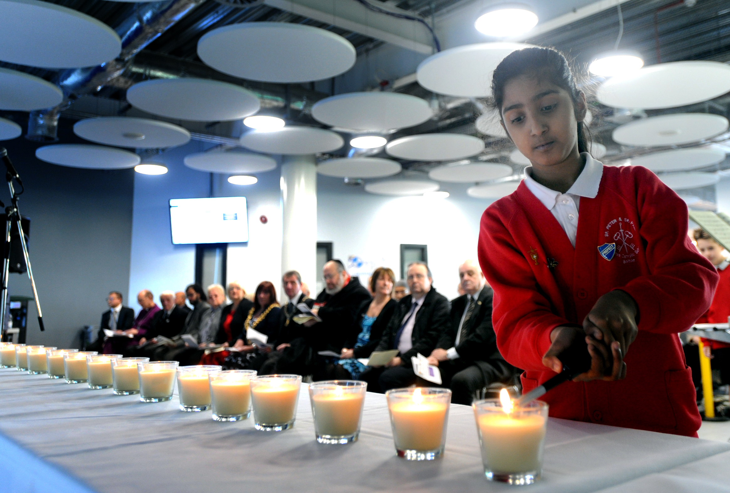 Angel Stephen aged 10 from St Peter and St Pauls CE School lights a candle at the Holocaust Memorial Day event at Bolton UTC.