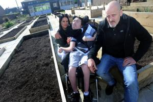 Eric Bromley with daughter Jessica Bromley and son Ryan who is a user of HFT, Mill Street, Farnworth which is set to close just after creating a new garden with funding money.