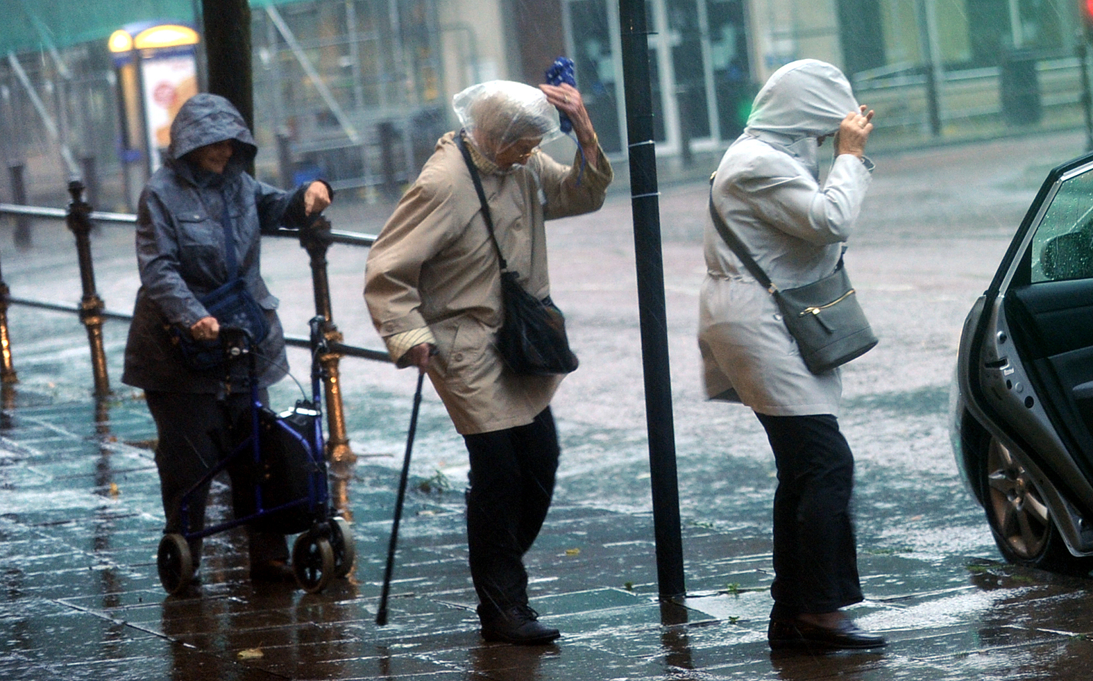 RAIN: Three ladies brave Storm Brian as it batters the North West