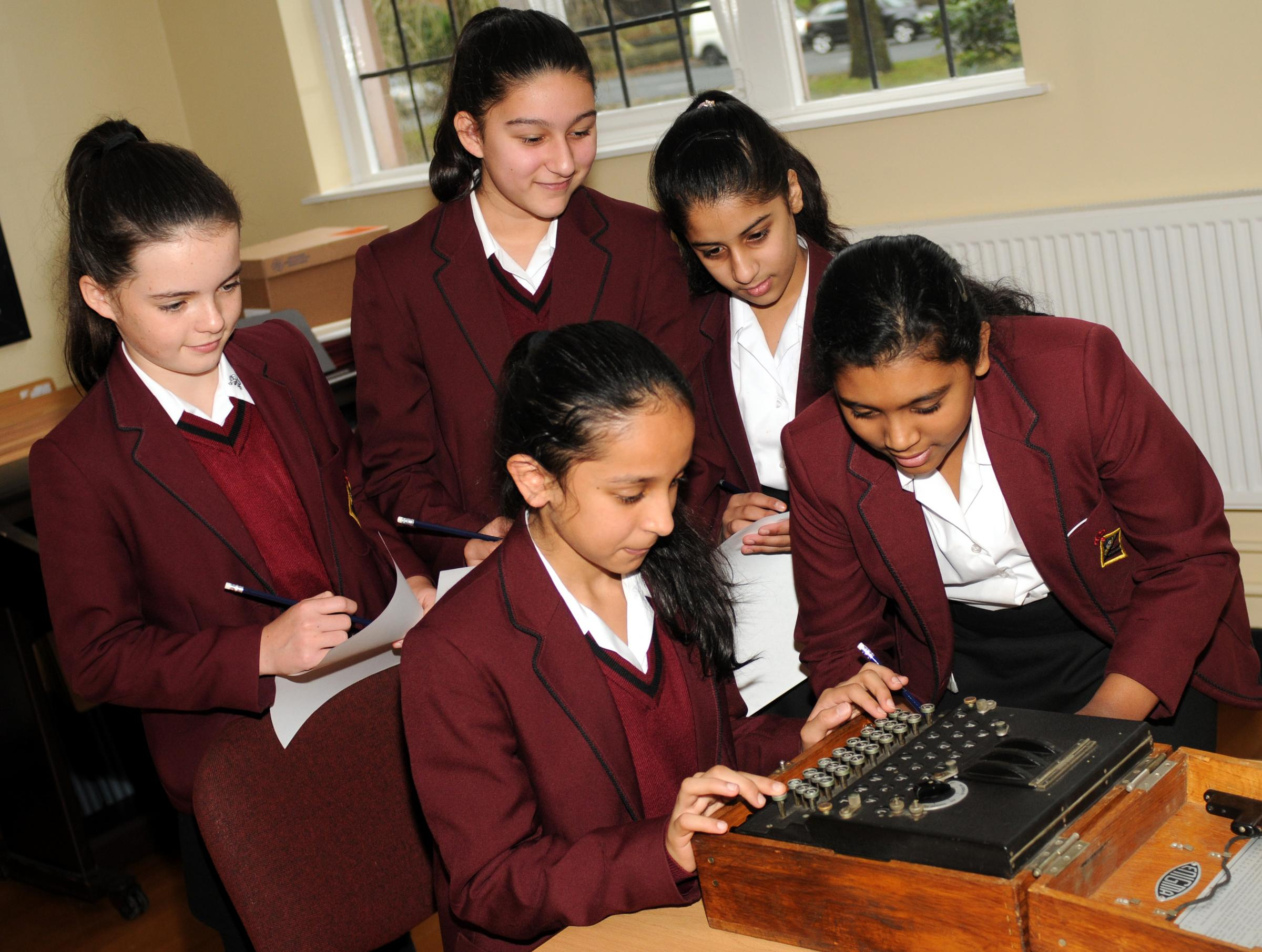 YOUNG MATHEMATICIANS: Iman Javaid, aged 11, types out a coded message on a genuine Enigma machine for fellow pupils, from left, Ruby Schofield, aged 11, Riya Hasija ,aged 12, Emaan Murtaz aged 11, and Adithi Prasad aged 11