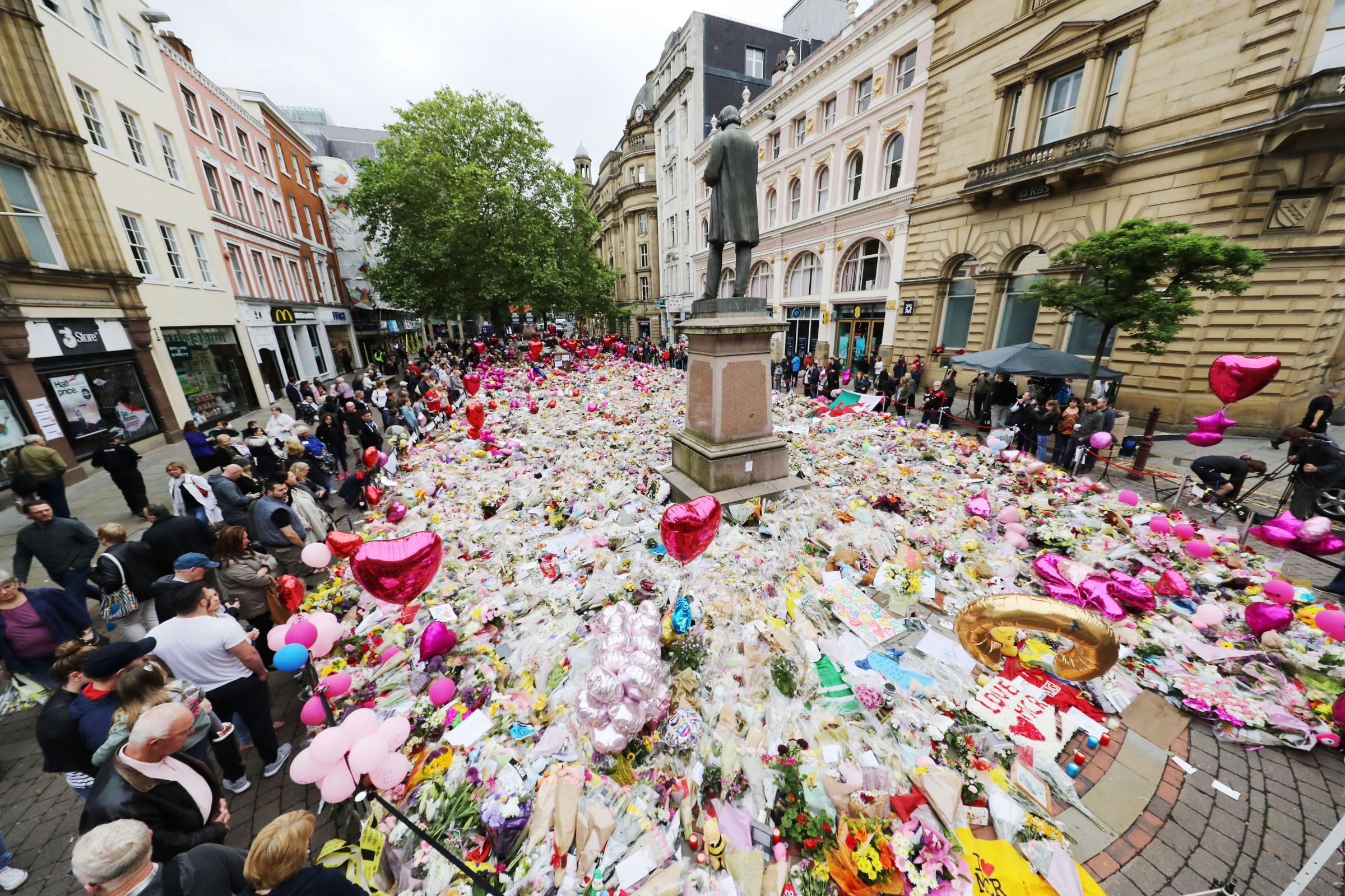 People look at flowers and tributes left in St Ann's Square in Manchester, a week after the Manchester Arena terror attack took place. PRESS ASSOCIATION Photo.