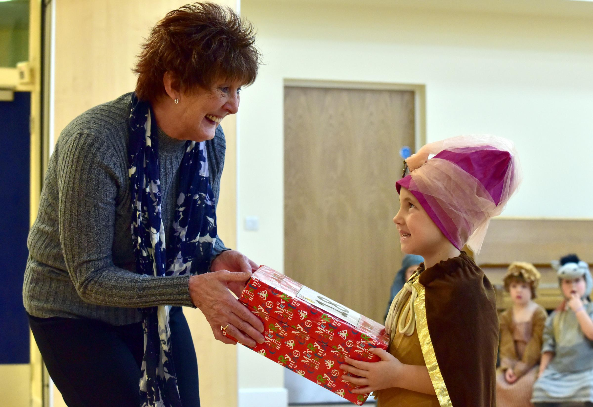 CARING: Bobby Williams, aged five, gives an advent present to Trish Davenport