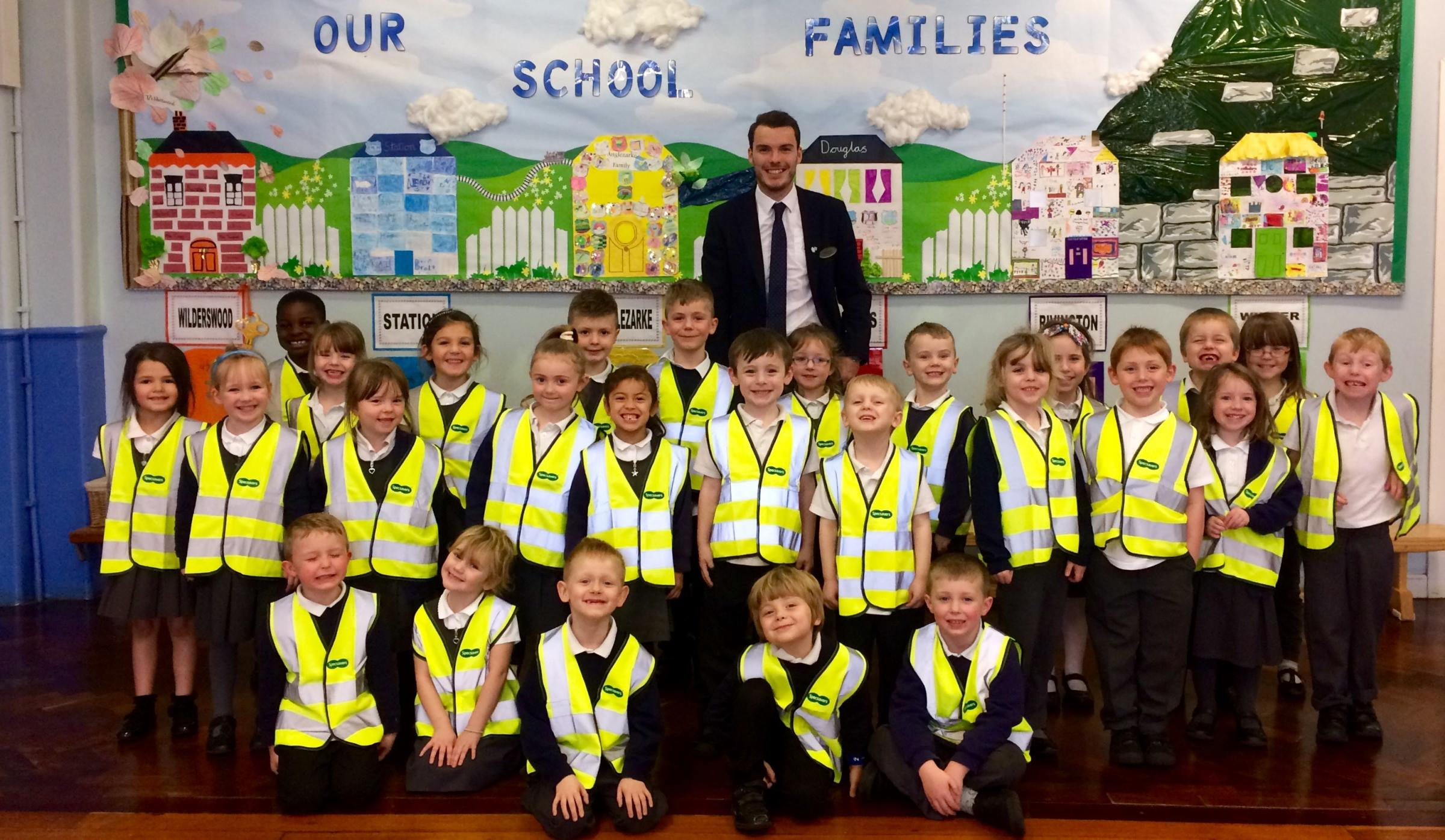 Martin Booth, manager of Specsavers in Crompton Place Shopping Centre, with children from Lord Street Primary school wearing their high-vis vests