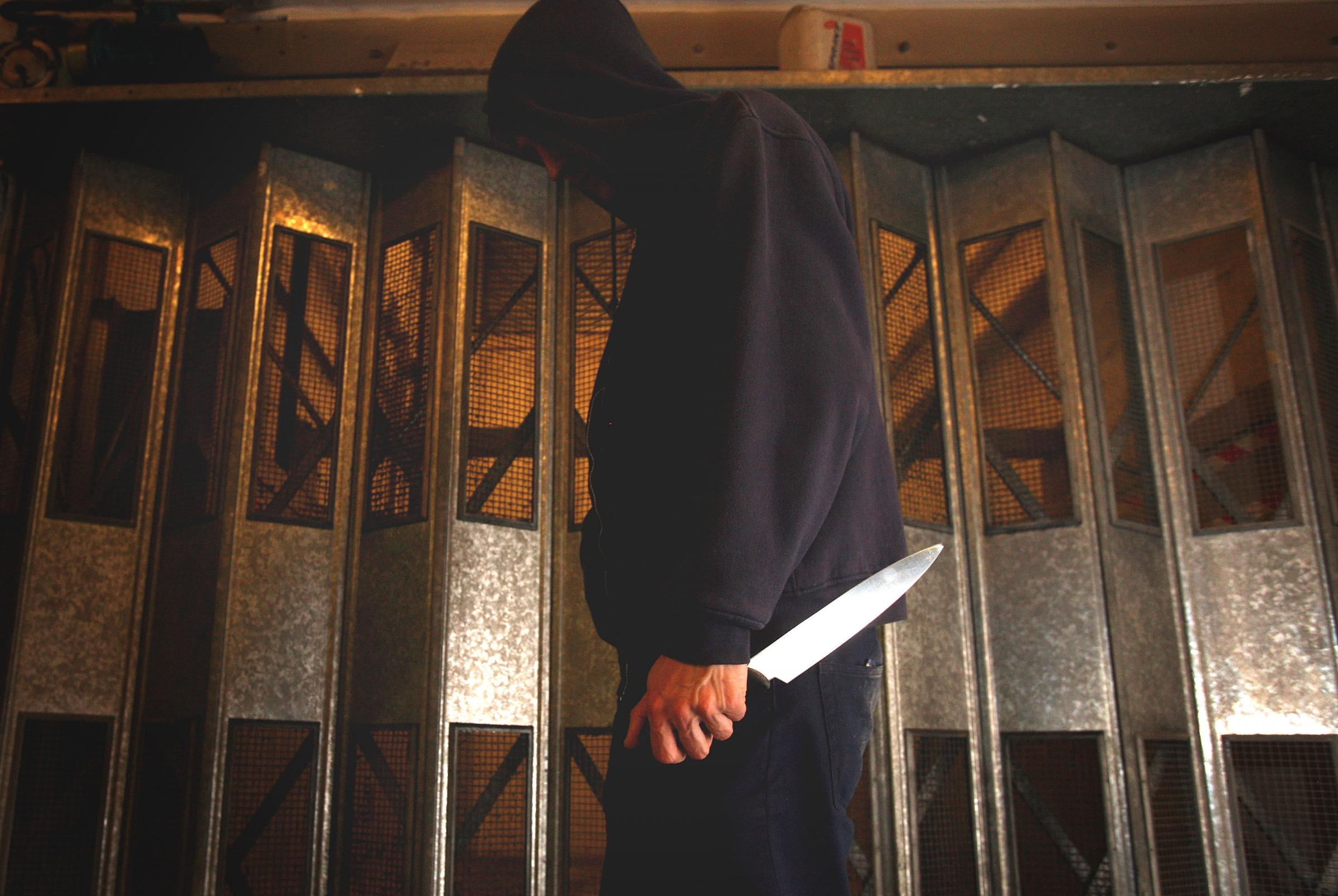 PICTURE POSED BY MODEL. ..Undated file photo of a man in a hoodie holding a knife. Knife and gun crime incidents recorded by police rose by more than 10% last year compared with 2015, the Office for National Statistics (ONS) has said. PRESS ASSOCIATION Ph