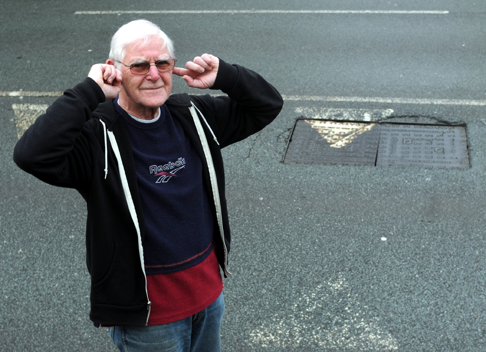 Edward Corley next to the broken manhole cover on Bradshaw Brow.