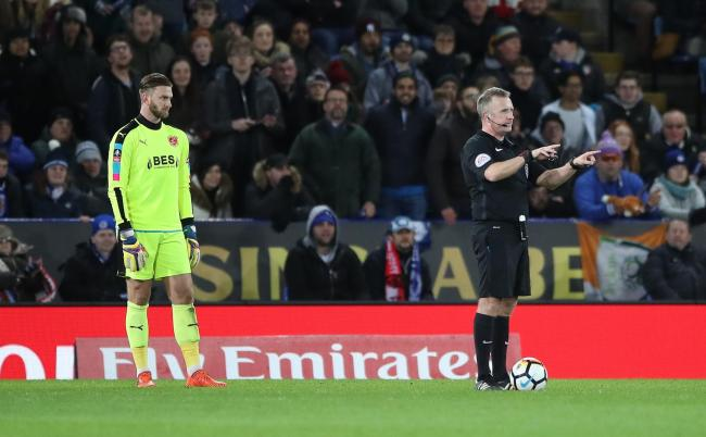 HISTORY MADE: Referee Jon Moss, right, consults VAR before giving Leicester City's second goal on Tuesday