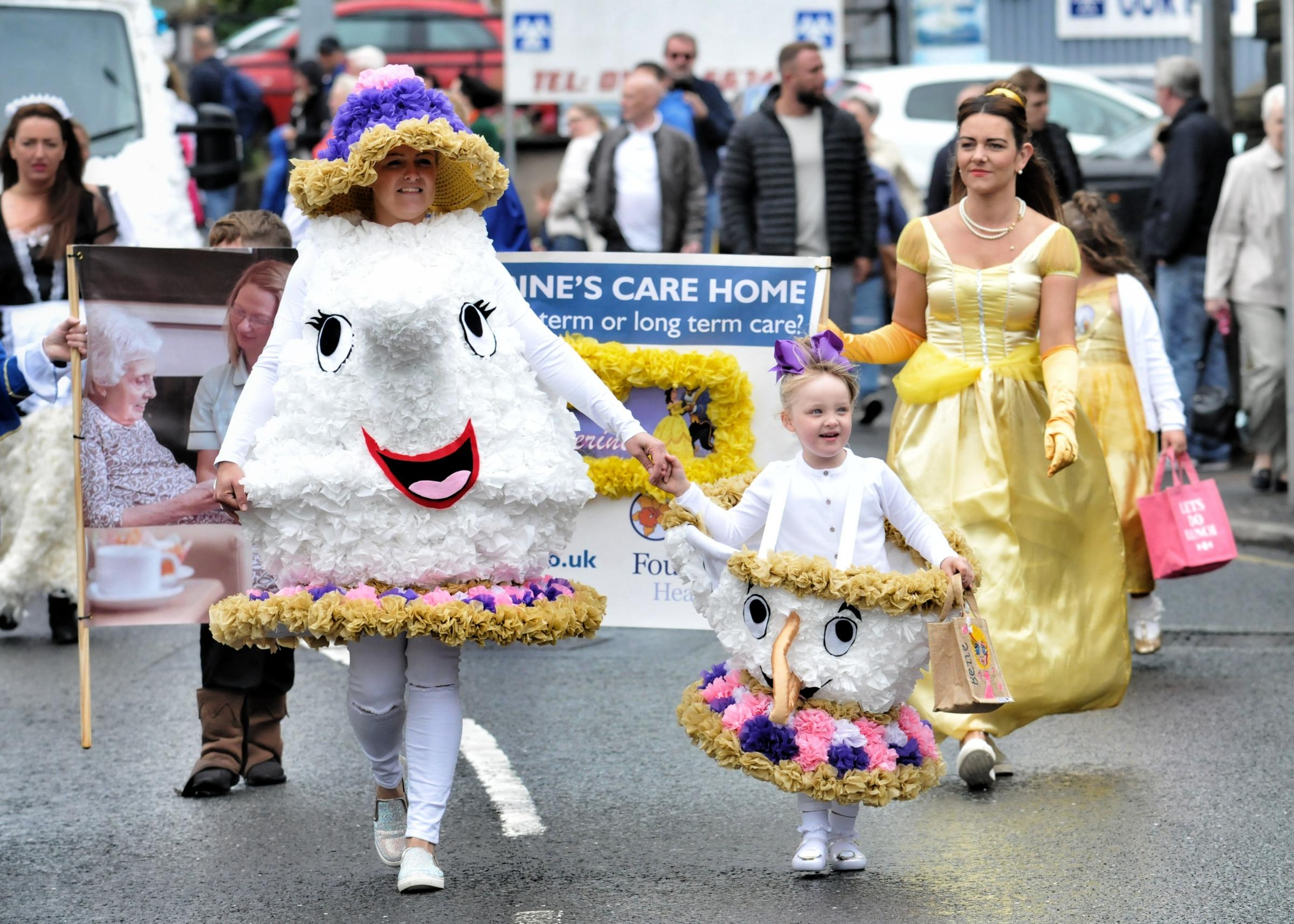 People dress as characters from Beauty and the Beast as they take part in the Horwich Carnival Parade.