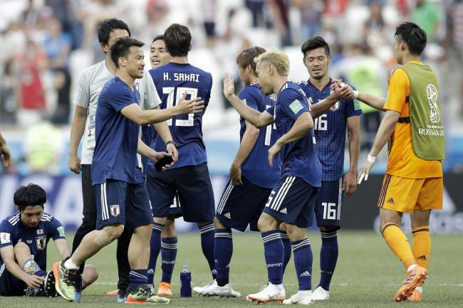 CELEBRATION: Japanese players congratulate each other after qualification but they should be ashamed for playing out time so feebly