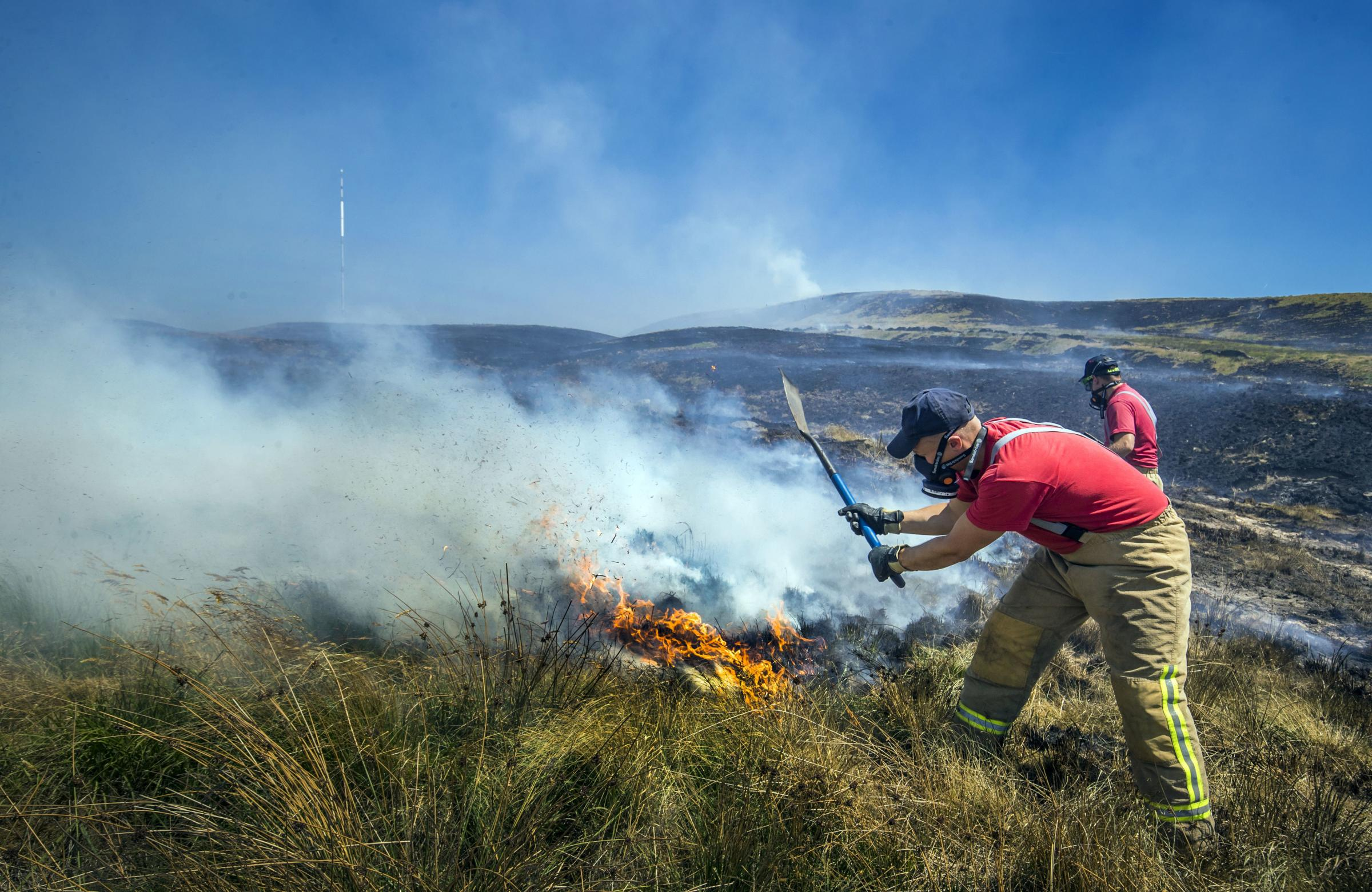 Firefighters continue to work on Winter Hill near Bolton. PRESS ASSOCIATION Photo. Picture date: Tuesday July 3, 2018. Fire chiefs declared a major incident on Saturday after two large-scale blazes either side of Winter Hill near Bolton merged because of