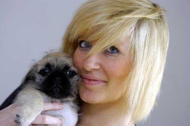 REUNITED: Michaela Wain and puppy Rooney share a cuddle after fire crews came to the rescue