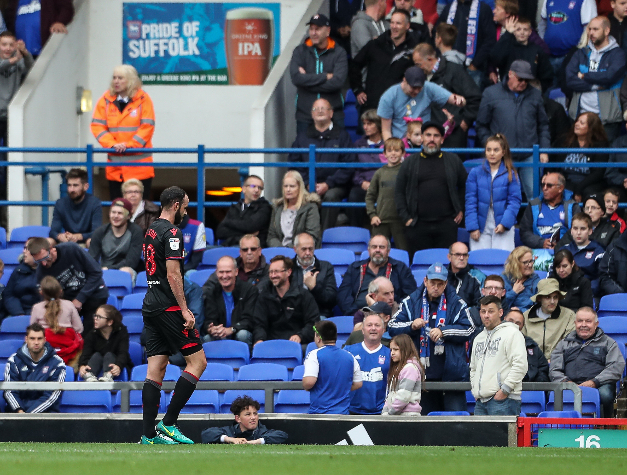 Marc Wilson walks off the field at Portman Road after his red card against Ipswich Town