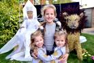WINNERS: Daisy Smith, aged nine, with her twin sisters Tilly and Lulla, aged three, beside the Pope family's winning residents entry