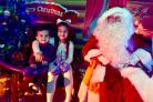 Aaliya Ali aged seven and Raees Ali aged two enjoy meeting Father Christmas in his grotto at Bolton's Winter Festival.