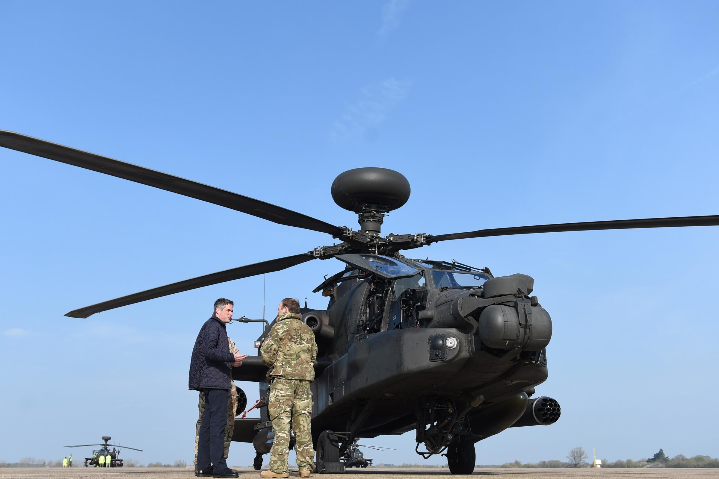 Defence Secretary Gavin Williamson next to an Apache helicopter at Wattisham Airfield in Suffolk