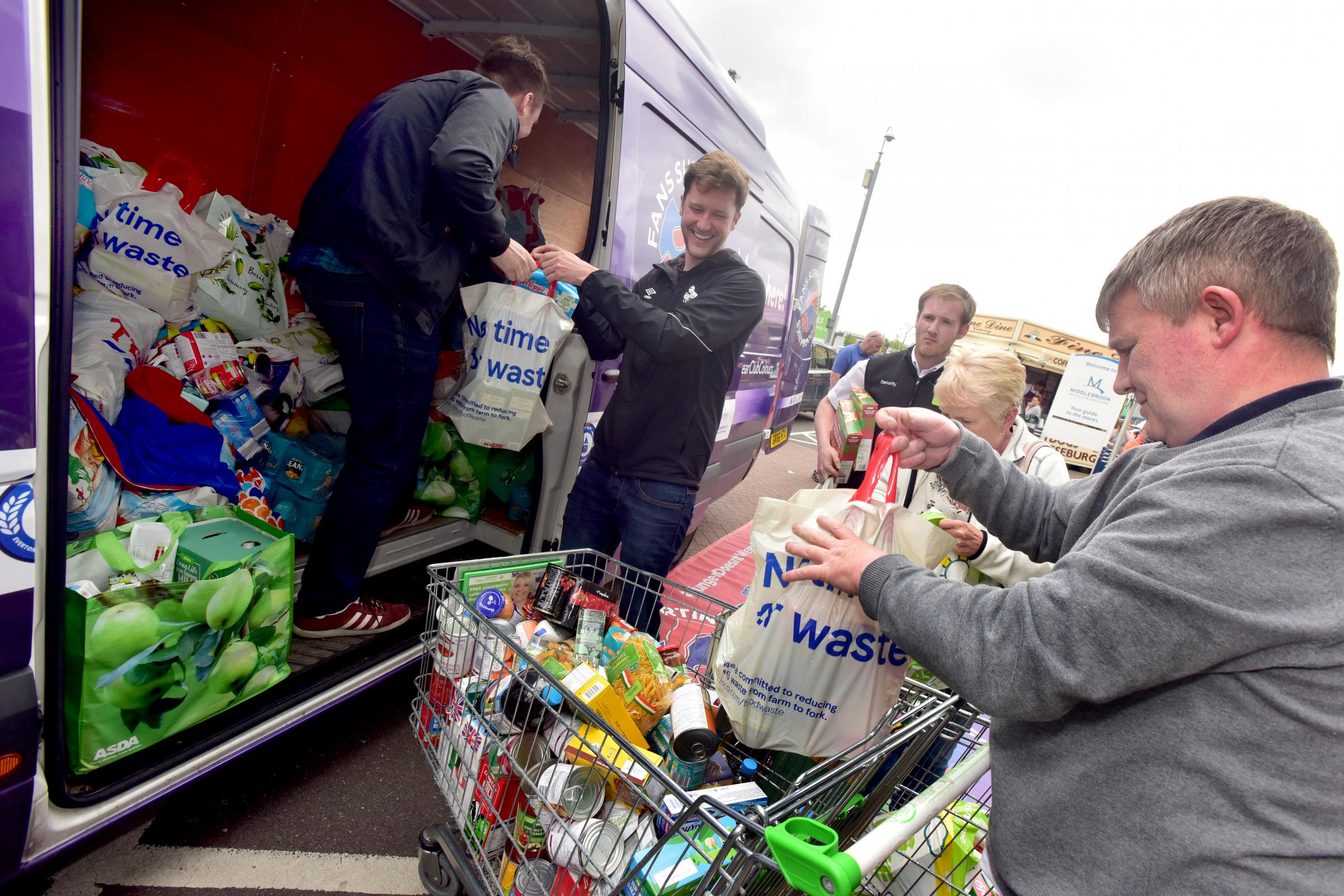 Football fans hand over bags of food for at Middlebrookto the foodbank van for the Bolton Wanderers staff